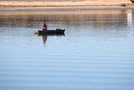 Man fishing in boat in the middle of a lake. Stock Photo