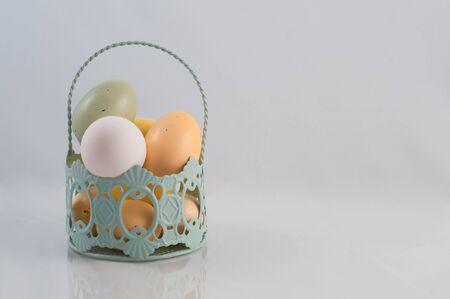 Easter eggs in basket with feathers Stock Photo