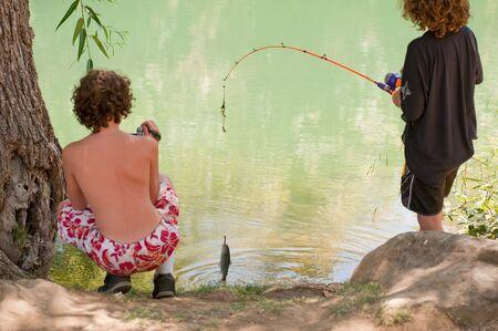 Jonge jongen vangsten zijn eerste vis, terwijl zijn broer het moment registreert.