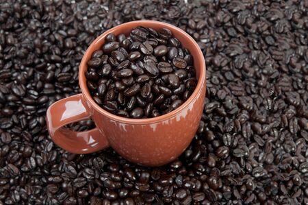 Coffee mug full of coffee beans on pile of coffee beans Stok Fotoğraf