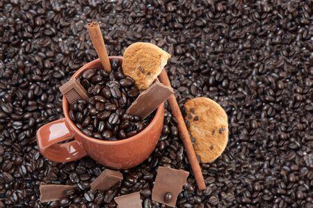 Koffiemok koffie bonen op stapel van koffiebonen vol met chocolade en kaneel stokken
