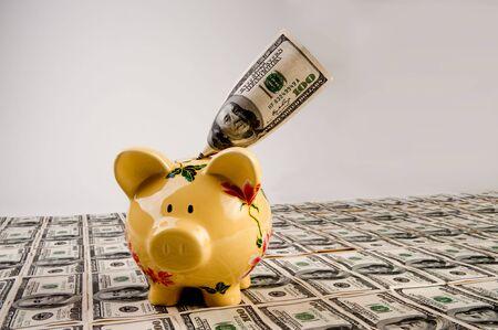 $100 rekeningen in Amerikaanse valuta met spaar varken op de top van geld Stockfoto
