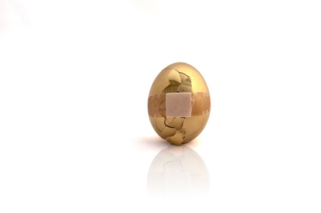 Broken golden egg with bandage over cracked area on white background photo