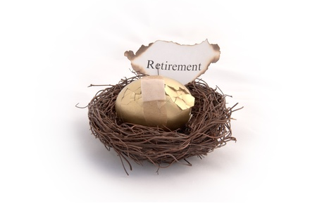 cracked egg: A golden egg sitting in a birds nest with a  piece of paper that reads retirement on it burning. Representing your savings going up in smoke Stock Photo