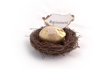 Een gouden ei zitten in een vogelnest met een stuk papier dat pensioen leest op het branden. Die uw spaargeld gaat in rook op