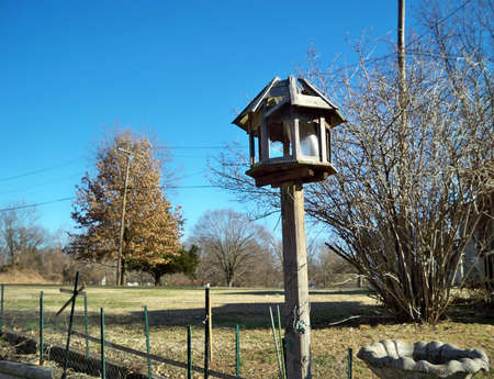 lanscape: old bird feeder against a brilliant blue sky