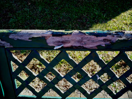 back of park bench with peeling green paint