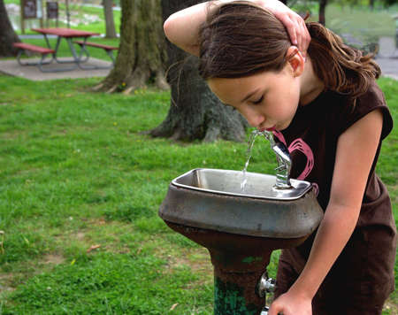 little girl drinking from fountain photo