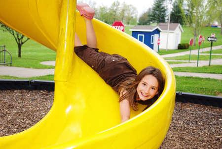 Smiling girl bellyflops on a slide Stock Photo