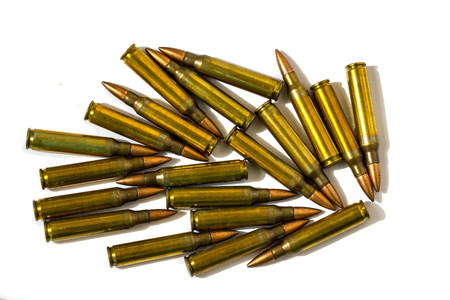 M16: 5.56x45mm NATO intermediate cartridges isolated on white background. Stock Photo
