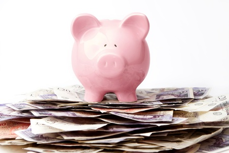 Piggy bank on stack of British Pounds Stock Photo - 9357330