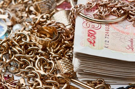 Gold jewellery on pile of British Pounds, saving concept