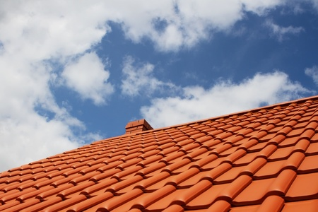 roofing: Brand new red rooftop against blue sky Stock Photo