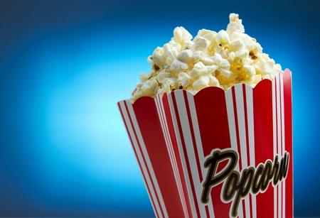 popcorn: Popcorn su sfondo blu, concetto di film Archivio Fotografico