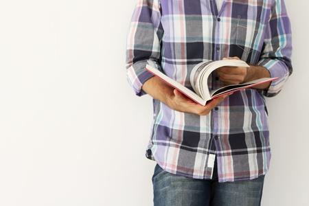 bible ouverte: Jeune homme contre le mur en lisant un livre