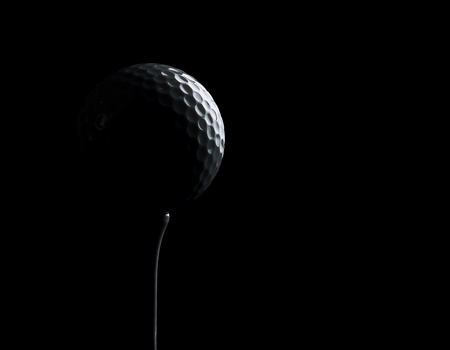 Golf ball on black background with copy space photo