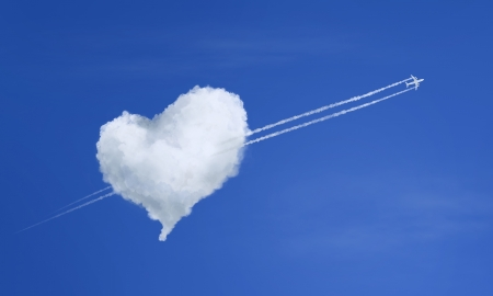 Airplane flying through heart shaped cloud photo