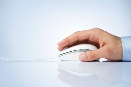 Male hand holding computer mouse with copy space