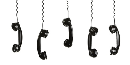 Rotary telephone handsets hanging in the air isolated on white photo