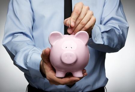 pieniądze: Mężczyzna rÄ™ka wprowadzenie monety do skarbonki