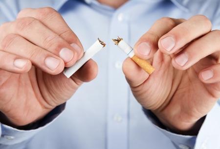 Beenden Sie das Rauchen, brechen menschliche Hände Zigarette