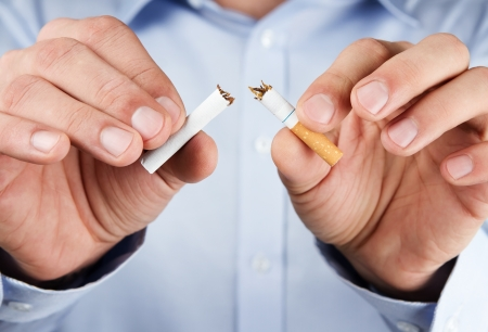 Quit smoking, human hands breaking up cigarette Stock Photo