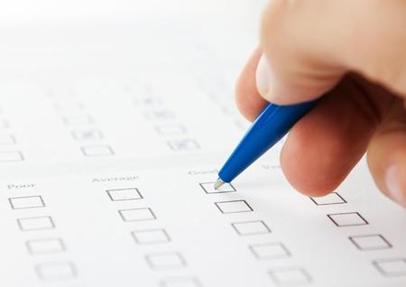 check list: Close up of human hand filling job application Stock Photo