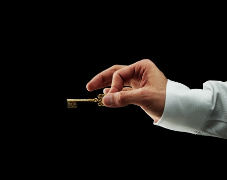 Human hand holding golden key Stock Photo - 11914431