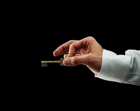 Human hand holding golden key photo