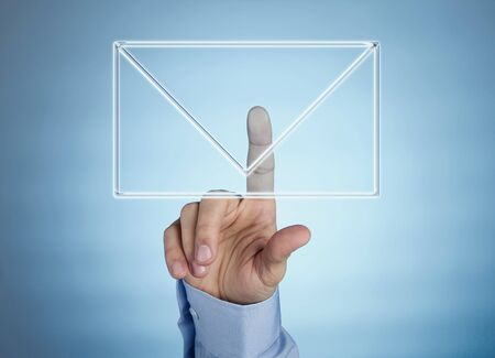 Male hand pressing mail icon on futuristic transparent display photo