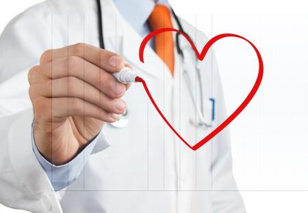 gezondheid: Mannelijke arts tekening hart symbool op het whiteboard Stockfoto