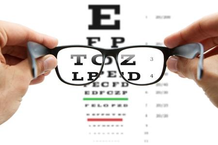 Mirando a través de las gafas en la tabla optométrica Foto de archivo