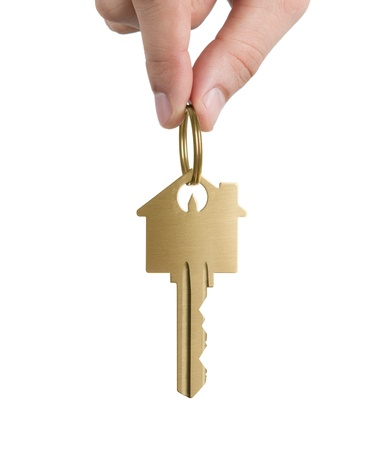 Human Hand Holding Key To A Dream House Isolated On White Background photo