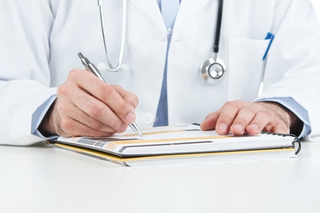 doctor's office: Close up of doctors hands filling documents Stock Photo
