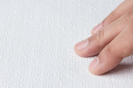 sense of sight: Close up of male hand reading braille text