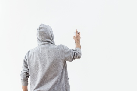 sudadera: El hombre joven se rocía pintura en el muro de hormigón, con copia espacio