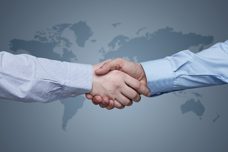Business handshake with world map in the background photo