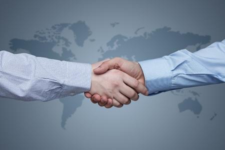 comercio: Negocios apret�n de manos con mapa del mundo en el fondo