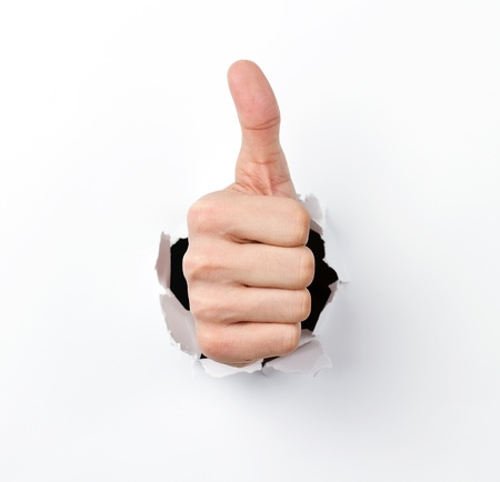 arms up: Thumbs up through the hole in paper sheet Stock Photo
