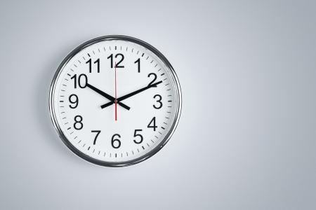 reloj de pared: Reloj de plata brillante que cuelga en la pared con espacio de copia Foto de archivo