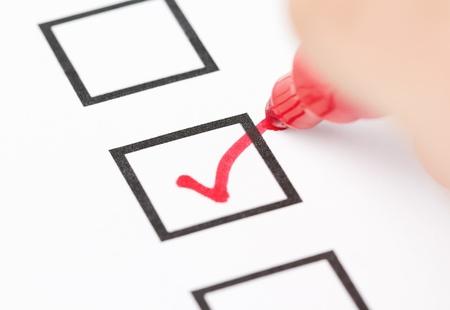 Macro shot of human hand drawing red check mark in checklist box photo