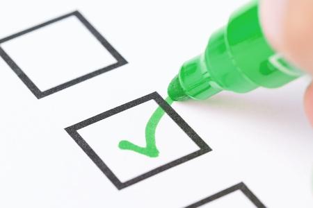 Macro colpo della mano umana disegnare segno di spunta verde nella casella checklist