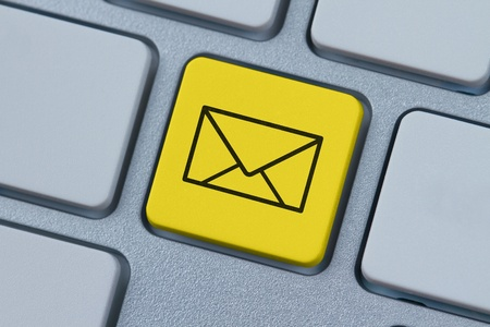 email us: Mail icon at computer key Stock Photo