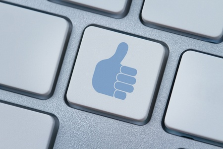 Thumbs up or like symbol at the computer keyboard Stock Photo - 13346092