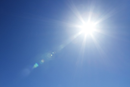 Sun with bright beams at the clear blue sky with copy space