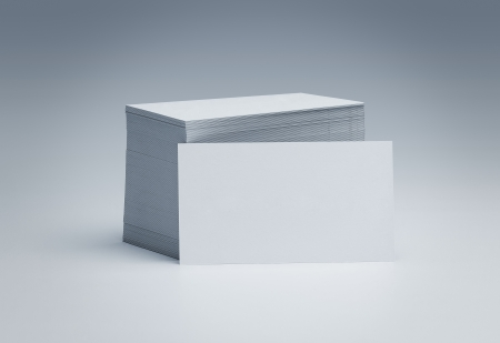 Stack of blank business cards over gray background with copy space photo
