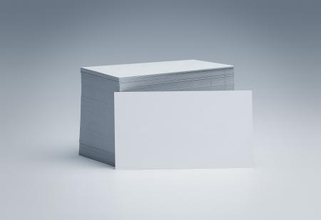Stapel blanco visitekaartjes over grijze achtergrond met een kopie ruimte