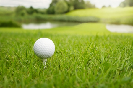 Golf ball on a tee against the golf course with copy space photo