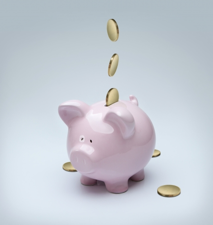 Golden coins falling down into a piggy bank photo
