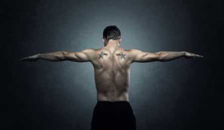 nude male: Young adult stretching out arms over dark background